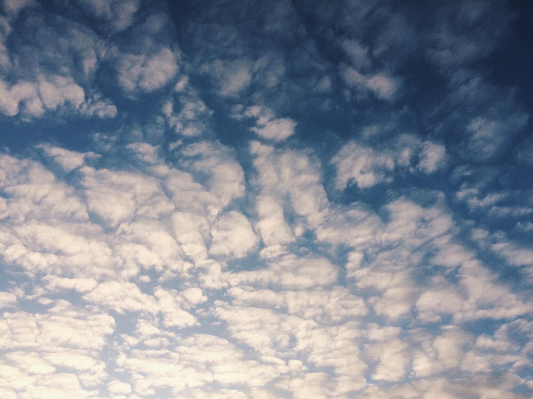 Himmel voller weißer Wolken, die teilweise das blaue des Himmels freigeben
