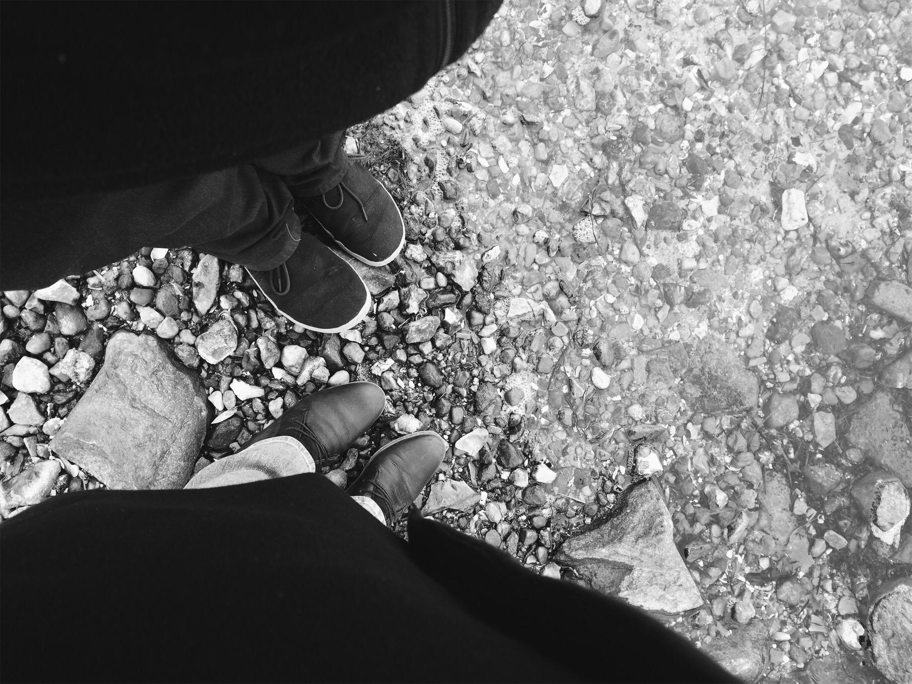 Blick von oben auf die Beine und Schuhe von zwei Menschen in Winterkleidung, die an einem Kiesstrand stehen. In der rechten Hälfte ist das heranschwappende Wasser zu sehen.