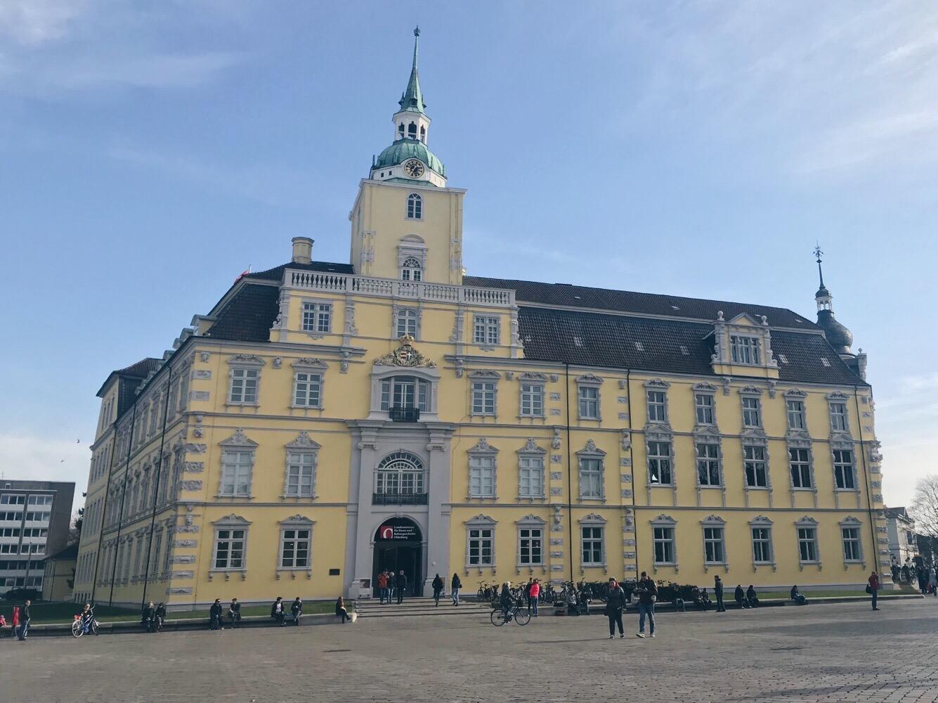Gelbes Schloss in Oldenburg mit einem wolkenfreien Himmel. Am Rand des Schlossplates sitzen einige Menschen.